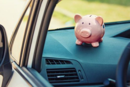 A piggy bank sits perched on the dash console of a car