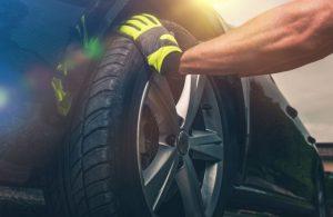 man replacing tires on a car