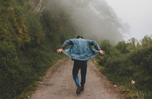 man walking on foggy trail flipping up ends of jean jacket
