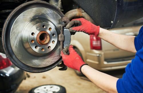 mechanic replacing brake pads on car