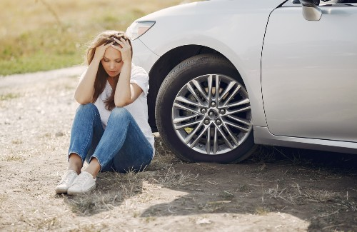 worried young woman sitting on ground next to broken down car