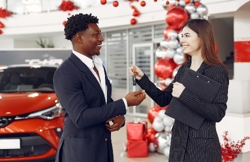 woman dealer handing keys over to young black man buying car