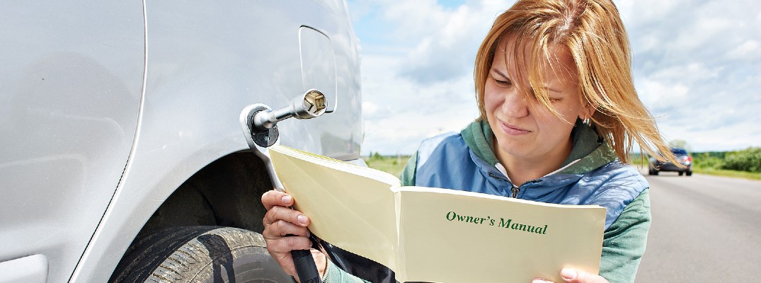 A stock photo of a person reading a vehicle's owner's manual.