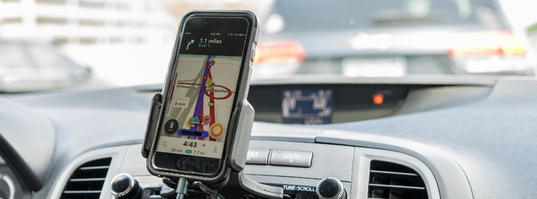 A photo of a smartphone attached to a dashboard showing navigation information.