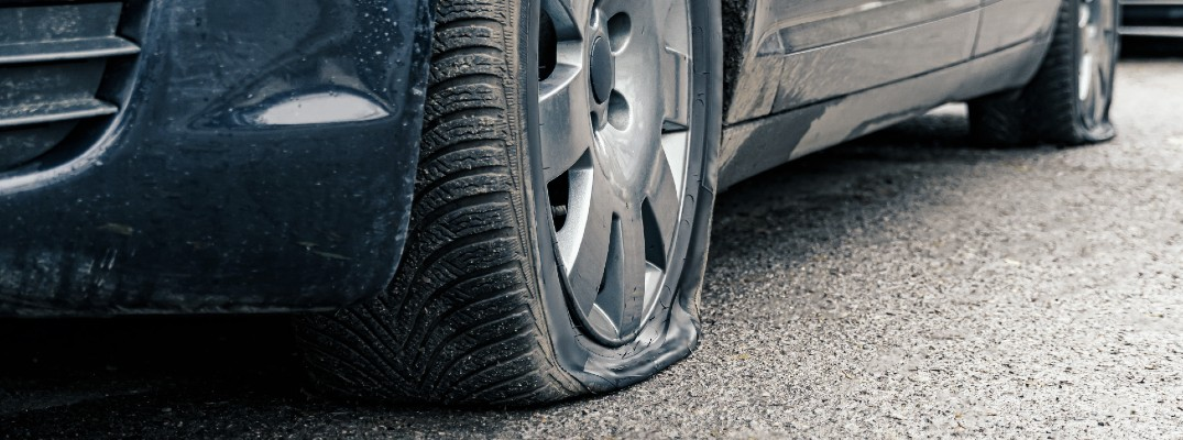 A stock photo of a car with two flat tires.