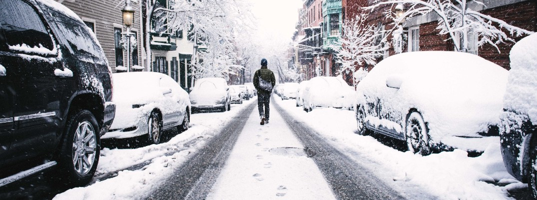 A stock photo of a person walking through snow because their car wouldn't start.