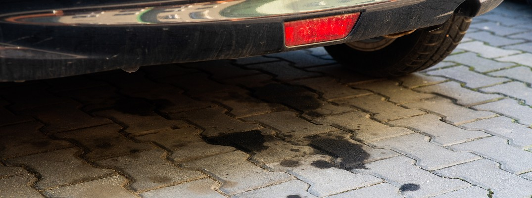 A stock photo of oil spots on a driveway under a car.