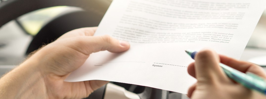 A stock photo of a person signing a contract in their car.