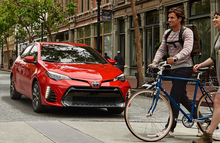 2018 Toyota Corolla In Red And Two Bikers
