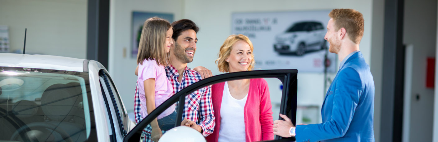 Cheerful family buying a car at a dealership