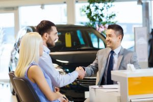Couple buying a car at a dealership