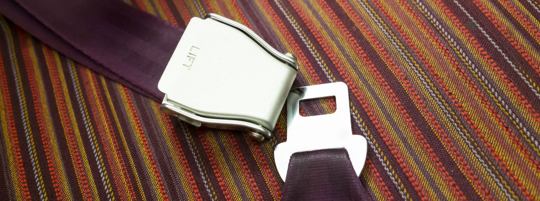 purple seat belt latches set atop a colorful floor carpet