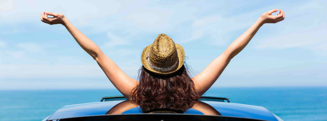 a woman with a straw hat extending and raising her arms out of a sun roof by a beach