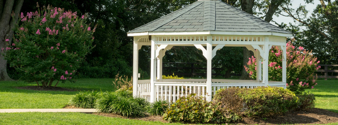 pavilion gazebo in a park surrounded by summer flowers and bushes in the sun