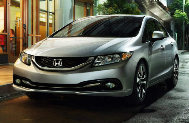 Exterior view of a silver 2013 Honda Civic parked on a city street at night