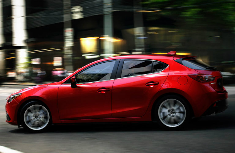 Exterior view of a red 2014 Mazda3 hatchback driving down a city street