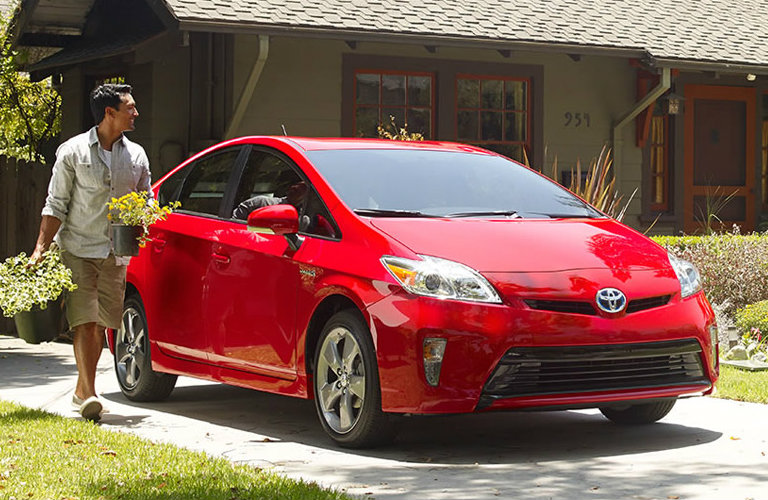 Exterior view of a red 2015 Toyota Prius parked in the driveway of a house in the suburbs