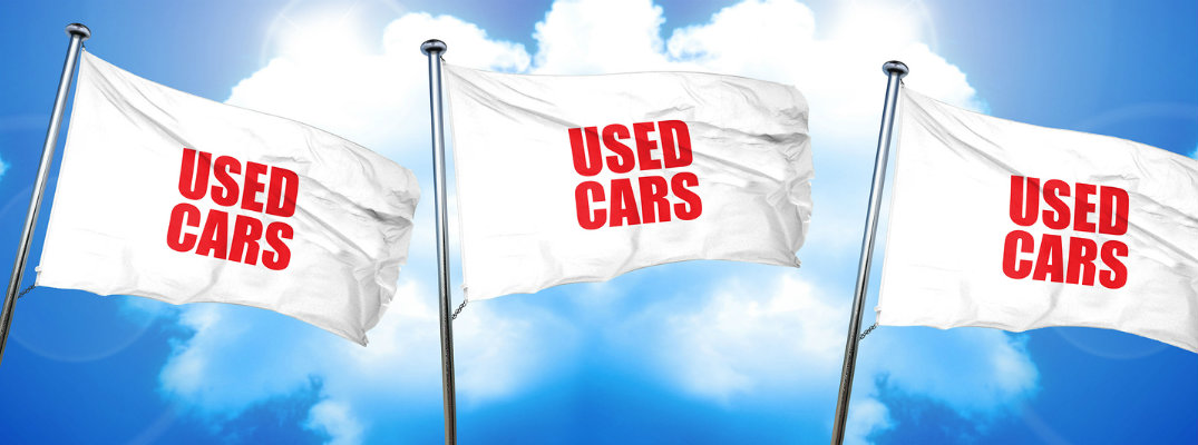 Featured image of three white flags with red text advertising used cars against a blue sky