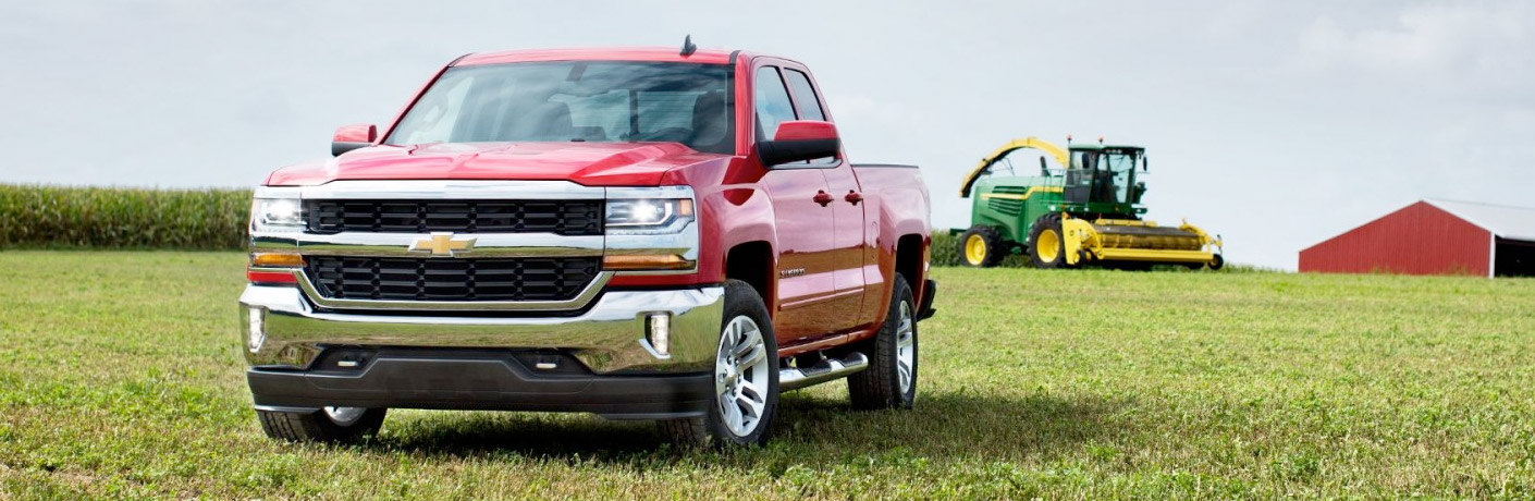 Exterior view of a red 2017 Chevrolet Silverado parked on a grassy farm field