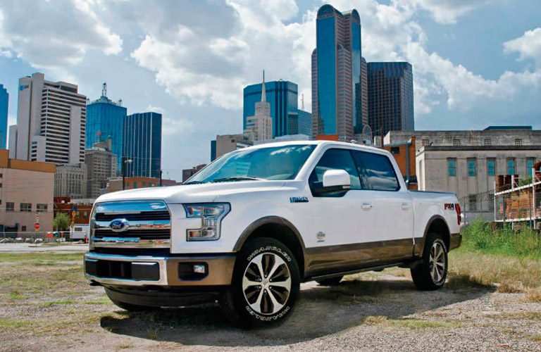Exterior view of a white 2017 Ford F-150 parked with city skyline in the background