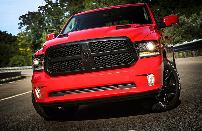 Exterior view of the front of a red 2017 RAM 1500 parked on a two-lane road