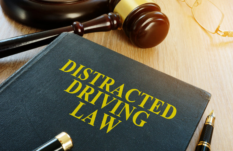 Image of a Distracted Driving Law book on a desk with a judge's gavel