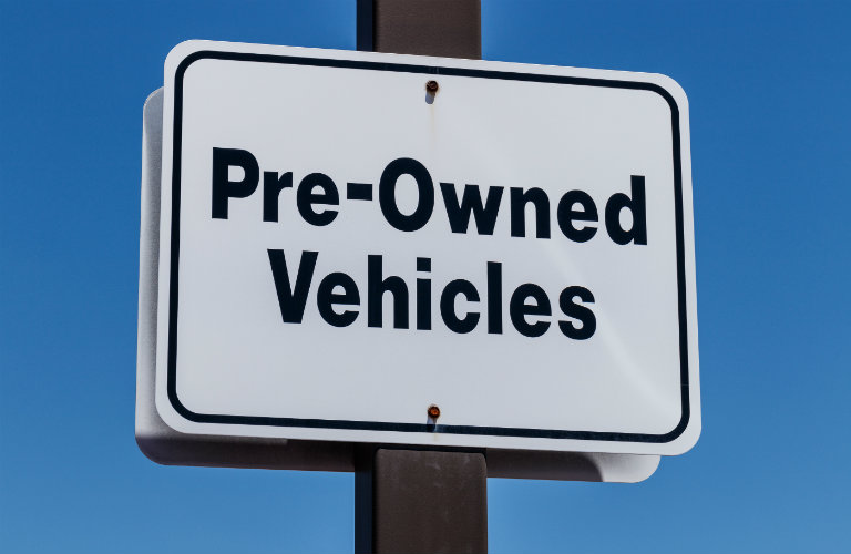 "White sign with black text advertising ""Pre-Owned Vehicles"""