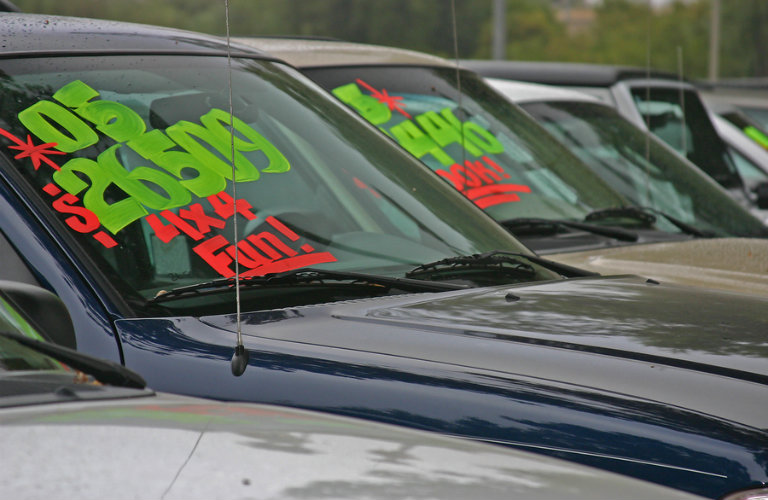 Exterior view of a few used cars in a row for sale at a used car dealership