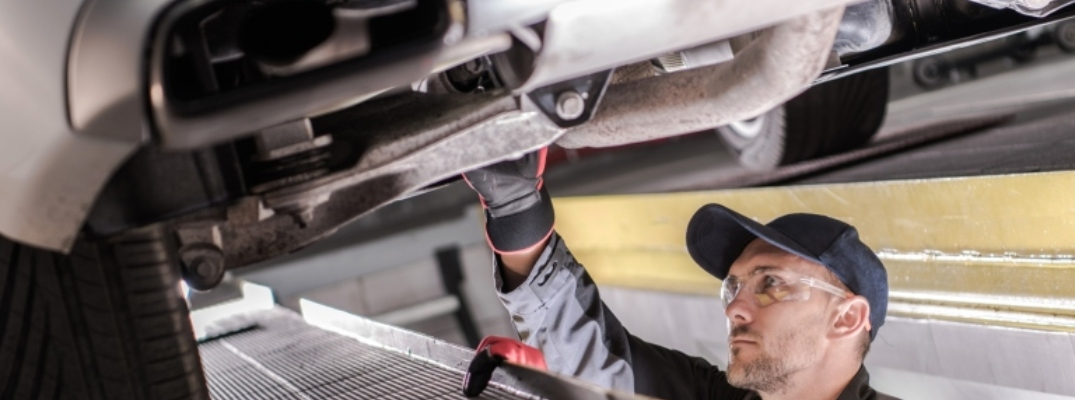 Image of a automotive technician inspecting a vehicle's undercarriage