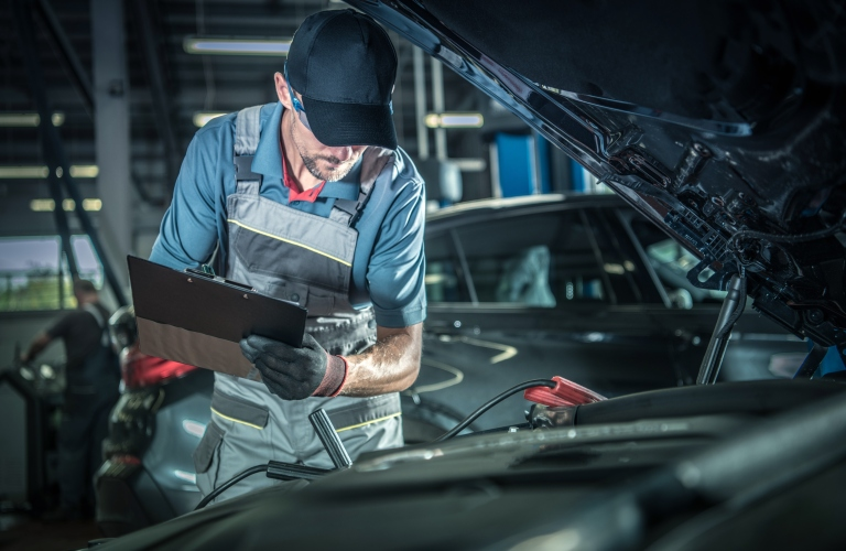 Image of a service technician conducting an engine inspection