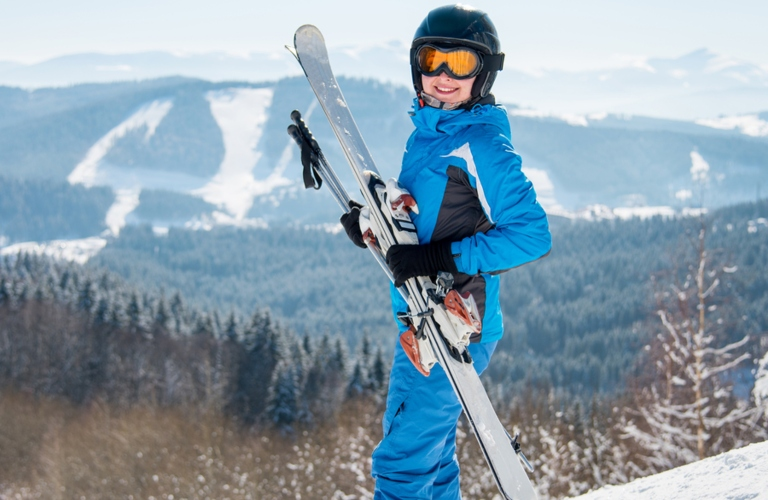 Image of a female skier holding her skis with large mountains in the background