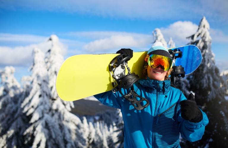 Image of a male snowboarder holding his snowboard on his shoulders with snow-covered trees in the background