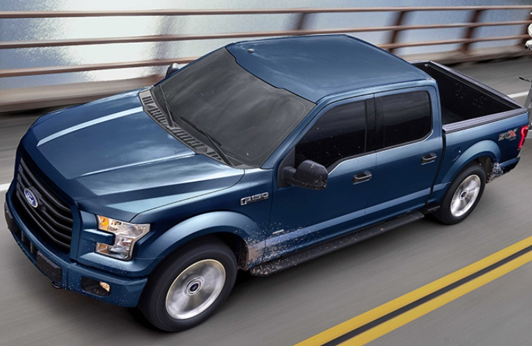 Exterior view of a blue 2017 Ford F-150 driving over a bridge
