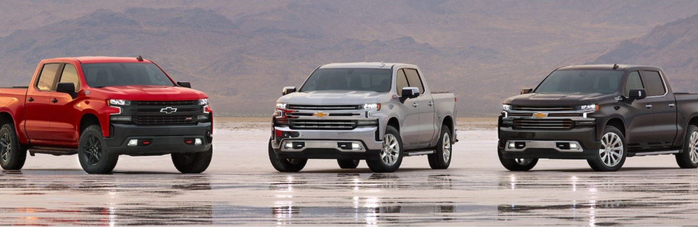 Exterior view of three 2019 Chevrolet Silverado models parked in and empty lot after rain