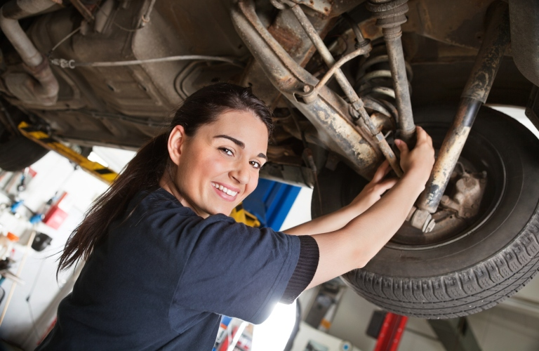 Female mechanic working underneath a vehicle while smiling at the camera