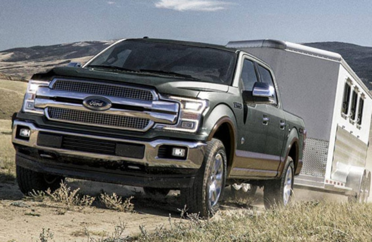 Exterior view of a green 2018 Ford F-150 towing a horse trailer