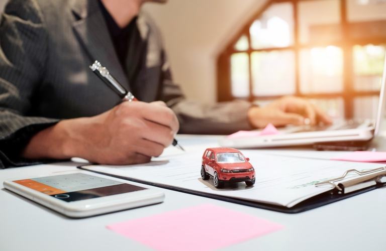 Image of an insurance broker filling out car insurance paperwork for a client