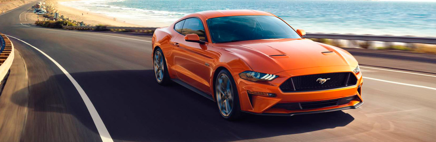 Exterior view of an orange 2018 Ford Mustang driving down a coastal highway