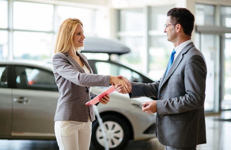 Image of a man and a woman shaking hands in an automotive dealership