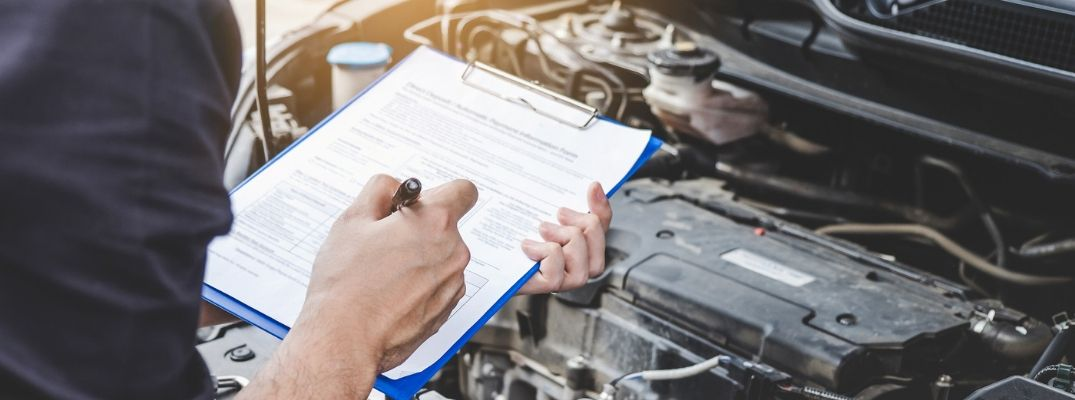 Image of a service technician filling out a service report while inspecting the vehicle's engine