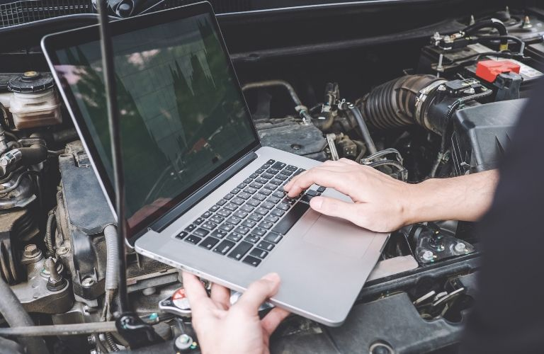 Image of a service technician running a computer diagnostic on a vehicle