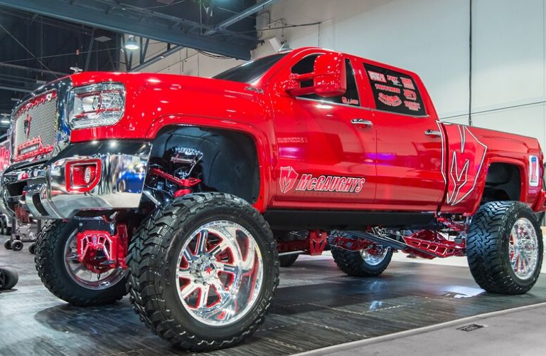 Exterior view of a red lifted GMC Sierra 1500 pickup truck