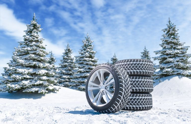 Image of a stack of four tires sitting in a snowy field