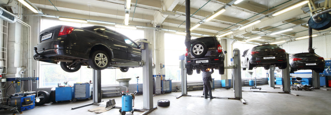 Four cars on lifts in an auto repair shop