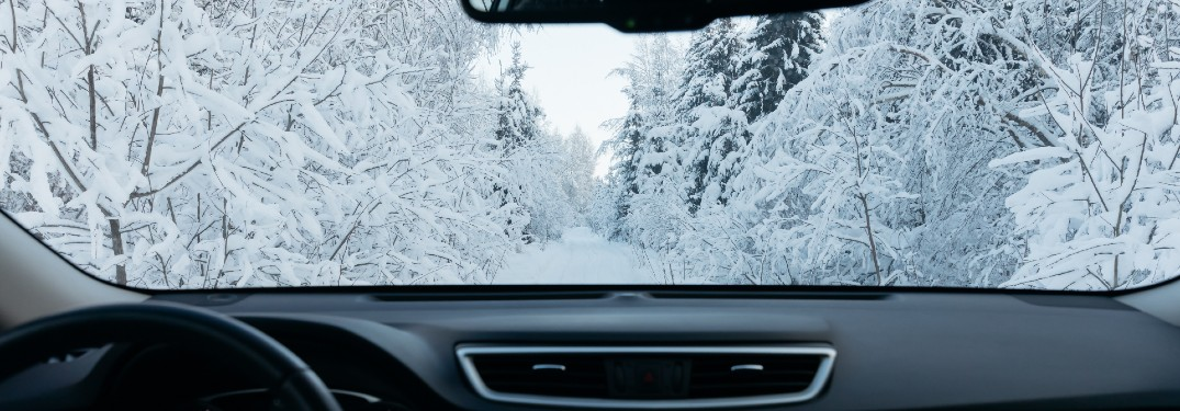 interior of car looking out windshield driving in snow covered area