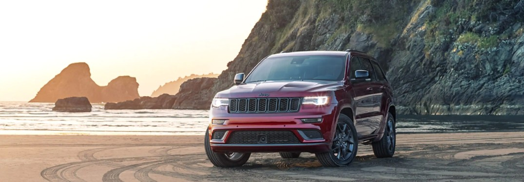 2020 Jeep Grand Cherokee red exterior parked on a beach with cliffs