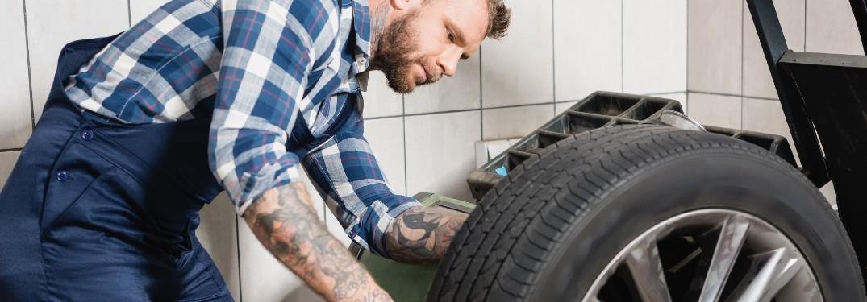 mechanic checking weight of wheel on tire balancing machine