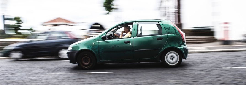 small green car driving on brick road