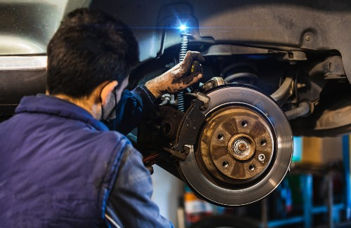 mechanic fixing brake rotor of car