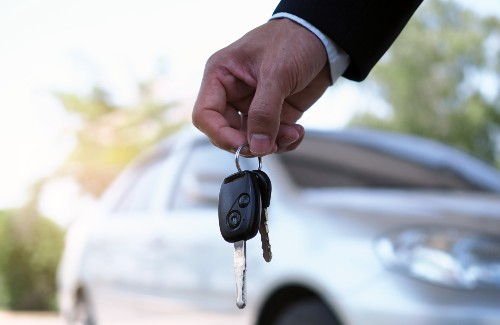 person holding keys of car with car in background